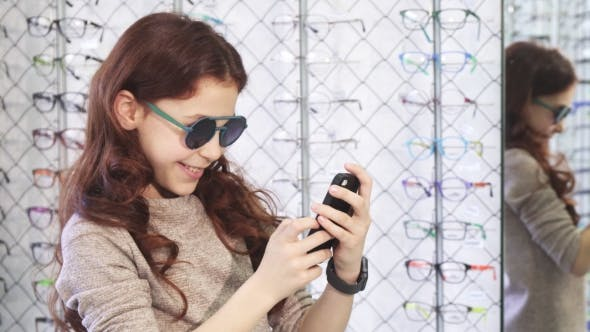 Thumbnail for Cute Little Happy Girl Taking Selfies at the Eyewear Store