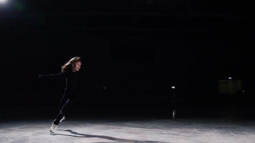 Une femme professionnelle, patineuse artistique à un costume noir aux compétitions de patinage artistique, effectue