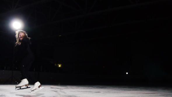 Thumbnail for A Professional Figure Skater Performs Ice Skating with a Jump in the Air with a Black Background in