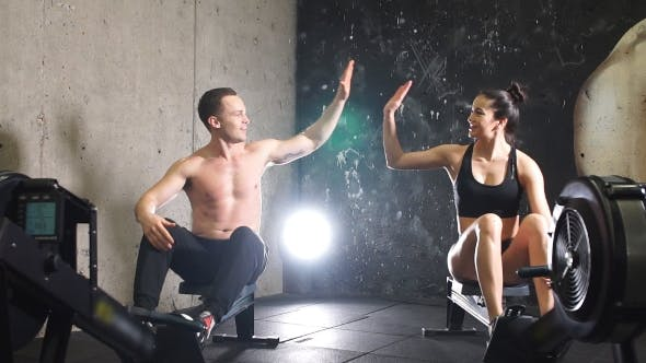 Thumbnail for Man and Woman Giving High-Five While Doing Exercises With Rowing Machine at Gym.