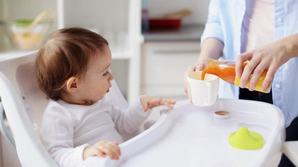 Thumbnail for Happy Mother with Spoon Feeding Baby at Home 1