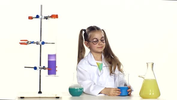Thumbnail for Cute Girl with Ponytails in Uniform and Round Glasses Evaluates Two Liquids, Standing By the Table