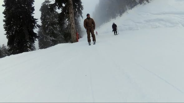 Thumbnail for Skier in Brown Bodusuit Riding on Mountain Hill