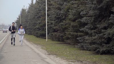 Young Woman and Man Runs Along Urban Road