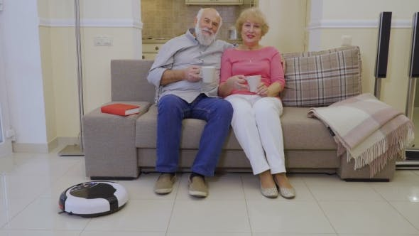 Thumbnail for Old Couple Relax at Sofa During Automatic Robot Clean the Floor in Living Room