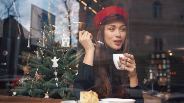 Thumbnail for Look From the Outside at Charming Woman in Red Hat Drinking Coffee Sitting in the Cosy Cafe