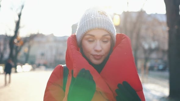 Thumbnail for Beautiful Woman in a Red Jacket Stands on the Street Covered with Snow in a Sunny Winter Day