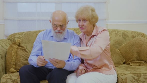 Thumbnail for Senior Couple Looks on Their Rent Bills Sitting at Sofa at Home