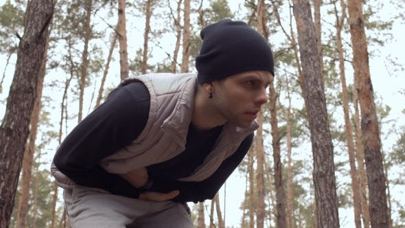Thumbnail for Young Man Has Pain in Stomach During Training in the Forest