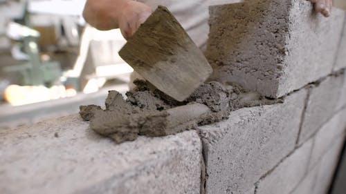 Builder ist imposant Gebäudelösung auf einer Wand aus Blöcken während Ziegelmauerwerk in einem