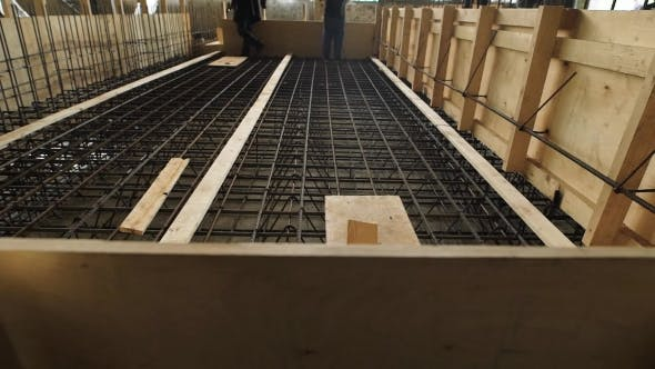 Laborers Are Standing and Walking over Reinforcing Cage Floor Slab in a Construction Site