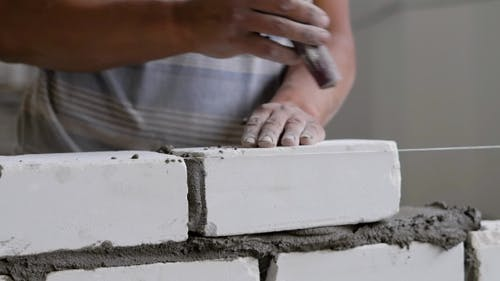 Builder Is Doing Brickwork, Hitting Over Brick By Trowel for Leveling and Taking Off an Excess