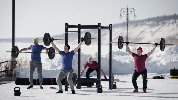 Thumbnail for Four Powerlifters Is Training in a Winter Day Outdoors, Lifting Heavy Rods, Standing on a Snowy