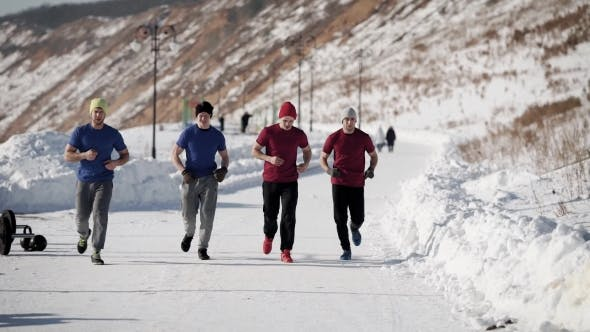 Thumbnail for Four Sportsmen Is Jogging in Cold Winter Day Over Snowy Path in Training Center Near Mountains