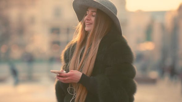 Thumbnail for Gorgeous Brunette Woman in a Gray Hat Standing in the Crowded City Street and Using Her Phone