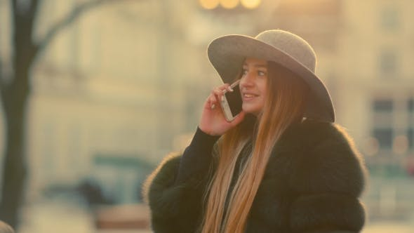 Thumbnail for Young Woman in a Bright Sunlight Uses Her Phone Smile Talks in the Phone