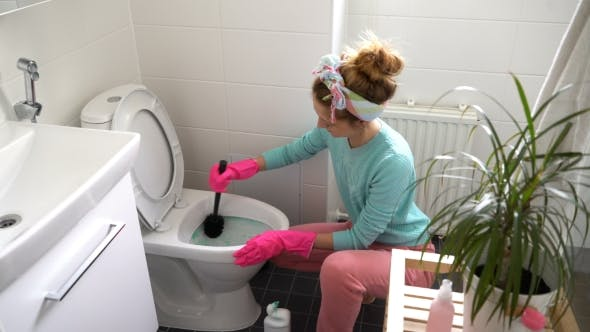 Thumbnail for Woman with a Rubber Glove Cleans a Toilet Bowl
