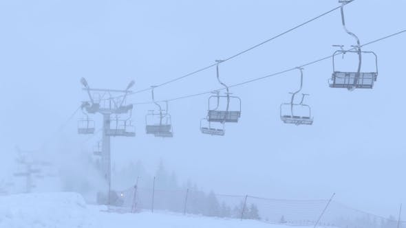 Thumbnail for Mountain Ski Slope and Operating Empty Chairlift in the Fog