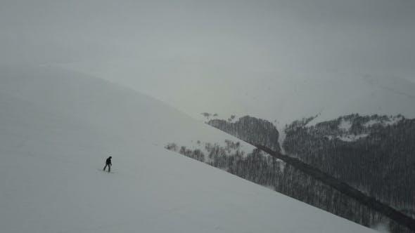 Snowboarder Descending By a Mountain Ridge. Birds Eye View Above White Powder Snow