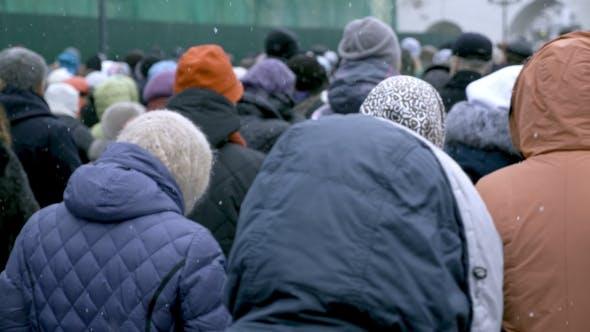 Une grande foule de gens se promène le long de la rue de la ville. L'hiver, la neige tombe.
