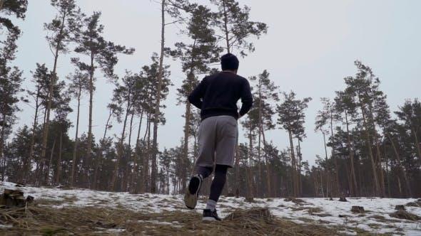 Junger Mann läuft auf dem Schnee Langlauf am Morgen