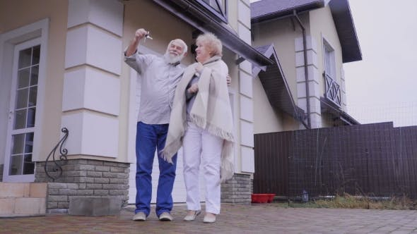 Thumbnail for Happy Old Couple with Keys From a New House Outdoors