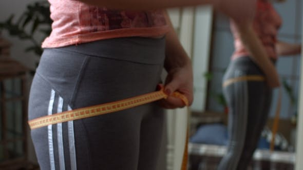 Thumbnail for Middle Aged Woman Measuring Her Hips with Tape