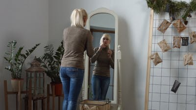 Sad Woman Looking in the Mirror at Her Wrinkles