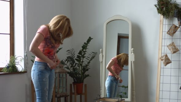 Thumbnail for Woman Struggling Trying To Fit Into Tight Jeans
