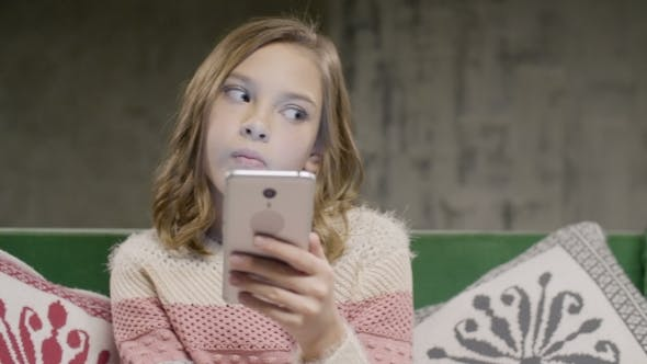 Thumbnail for Young Girl Holding Phone in Hands Sitting in Room