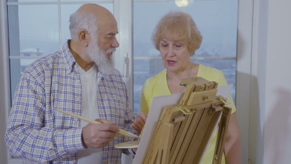 Thumbnail for Senior Man with Senior Woman Are Drawing Picture on Easel