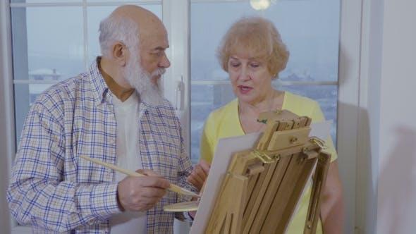 Senior Mann mit Senior Frau zeichnen Bild auf Staffelei