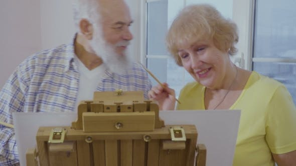 Thumbnail for Senior Man Has Fun with His Wife Drawing the Picture on Easel