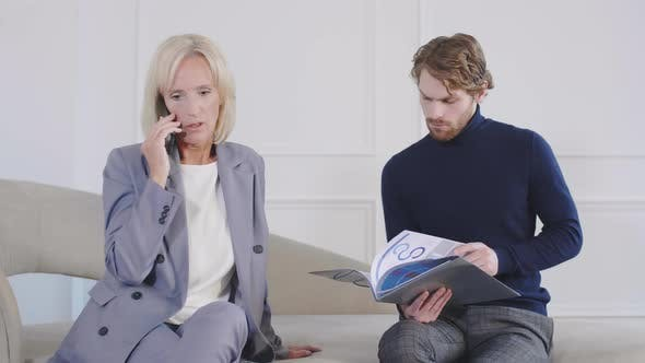 Thumbnail for Middle-aged Businesswoman and Her Male Colleague Working
