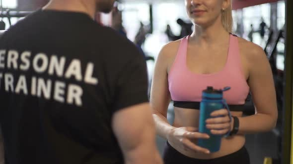Thumbnail for Attractive Female Client Talking to Fitness Coach After Finishing Workout