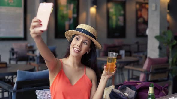 Portrait of Young Brunette Woman Taking a Selfie Photo From Cell Phone in Pub Bar