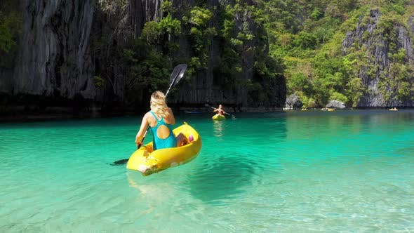 Cover Image for Woman Kayaking in a Tropical Big Lagoon with Clean Water, Tropical Forest, Rocks in El Nido Island
