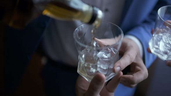 Thumbnail for Elegant Businessman Pouring Whiskey Into Glass