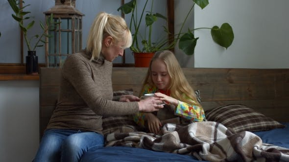 Thumbnail for Caring Mother Giving Her Ill Daughter Hot Tea
