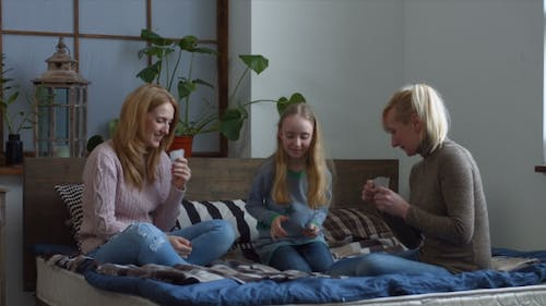 Joyful Family with Child Playing Cards on the Bed