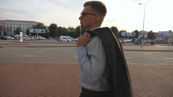 Thumbnail for Profile of young businessman walking at street near auto parking. Business man commuting to work.
