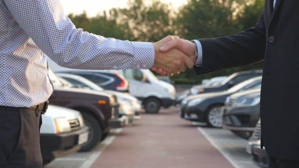 Thumbnail for Two Businessmen Shaking Hands of Each Other with Cars in Parking at Background.