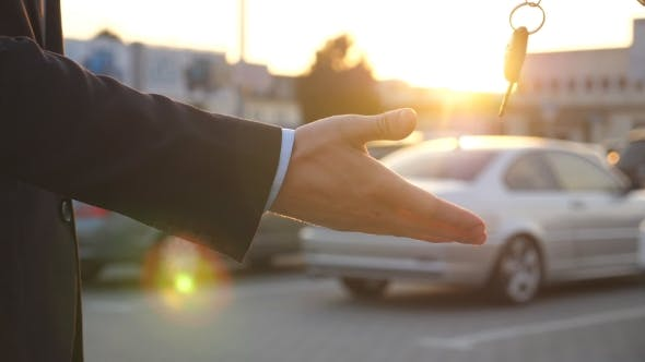 Male Hands Giving Keys of Car to His Friend. Arm of Businessman Passed Car Key