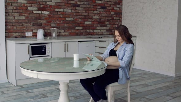 Thumbnail for Happy Pregnant Woman Sitting at a Glass Kitchen Table Drinking Coffee and Using the Tablet Computer.