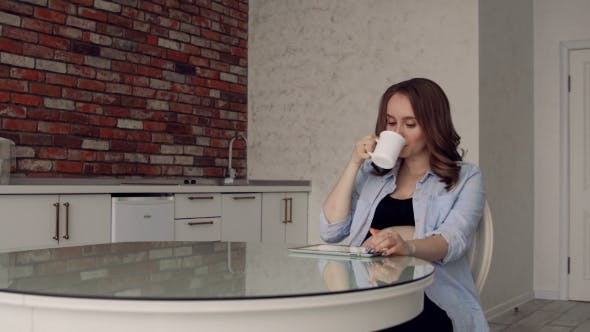 Thumbnail for Happy Pregnant Woman Sitting at a Glass Kitchen Table Drinking Coffee and Using a Tablet Computer