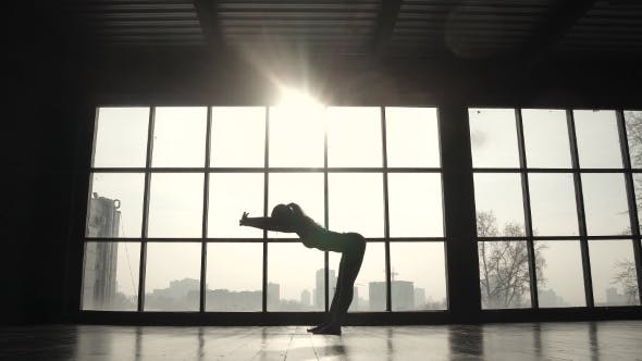 Thumbnail for Young Flexible Girl Doing Warm-up Before Training on the Background of a Large Window