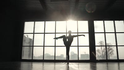Silhouette of a Gymnast on the Background of a Large Window