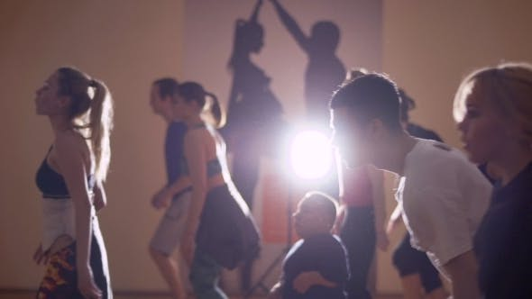 Thumbnail for Young Guys and Girls Performs a Dance in the Light of Lamp in Studio
