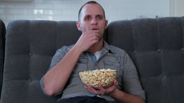 Thumbnail for Man Watching TV and Eating PopCorn