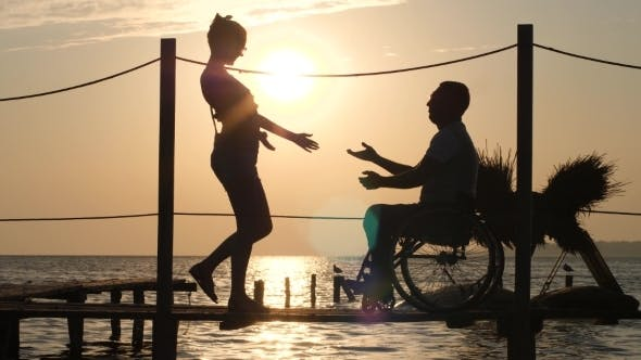 Thumbnail for Silhouette of Disabled Man and Woman Against Sun, Romantic Meeting on Waterfront